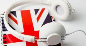 formation anglais sur se perfectionner ses compétences orales en anglais- casque et carnet avec drapeau anglais