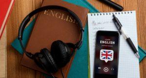 """Un casque avec un portable posés sur une table et des cahiers. Sur le portable on retrouve la phrase """"Learn English"""" pour rappeler la formation anglais à distance"""